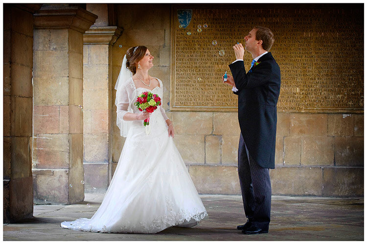 Emmanuel College wedding groom blowing bubbles smiling bride