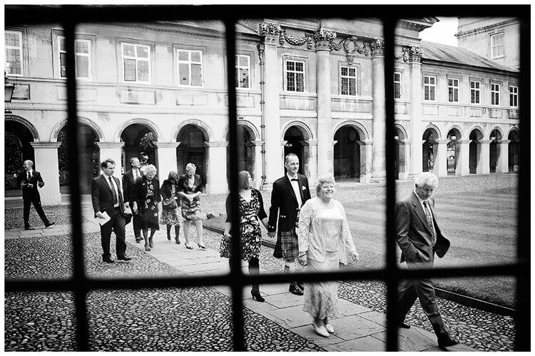 Emmanuel College wedding walking guests viewed through window