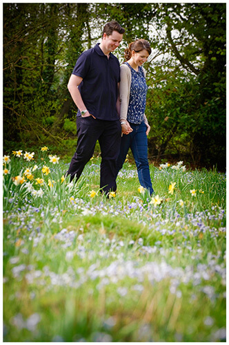 Fanhams Hall pre-wedding couple walking in filed of wild flowers