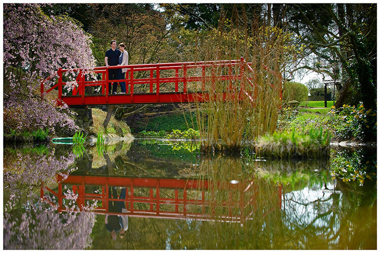 Fanhams Hall pre-wedding couple standing on red bridge over pond