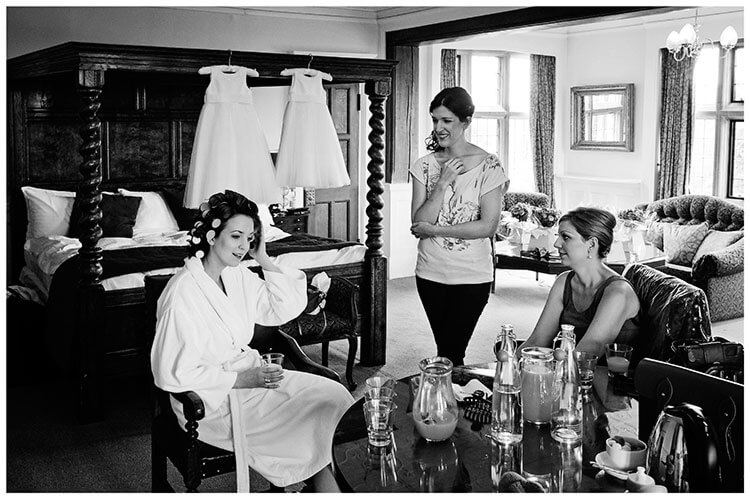 Fanhams Hall wedding bride in rollers talking to bridesmaids