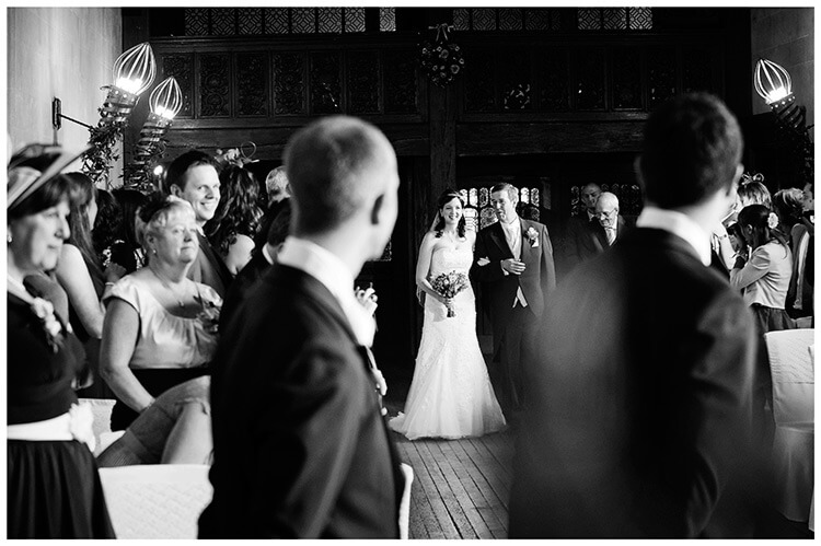 Fanhams Hall wedding bride enters on fathers arm groom watches