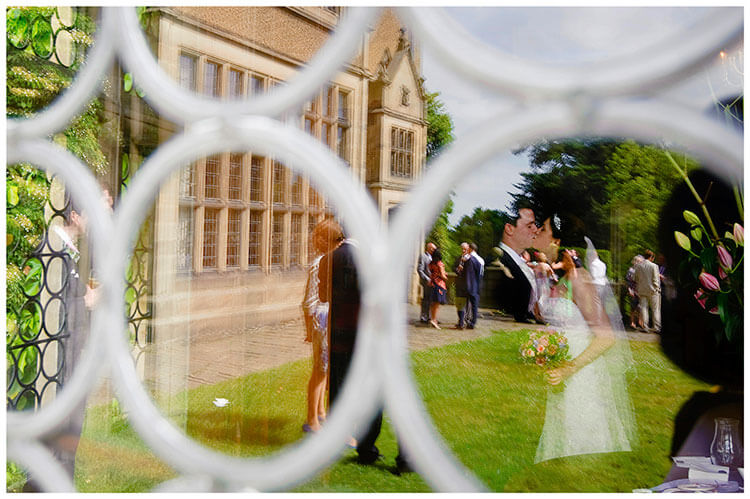 Fanhams Hall wedding bride groom kiss outside reflected in window