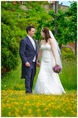 Fanhams Hall wedding bride groom standing in yellow flowers