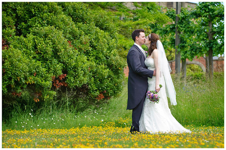 Fanhams Hall wedding bride groom romantic kiss in yellow flowers