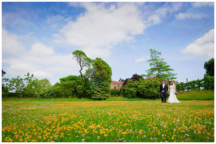 Fanhams Hall wedding bride groom romantic walk through yellow flowers