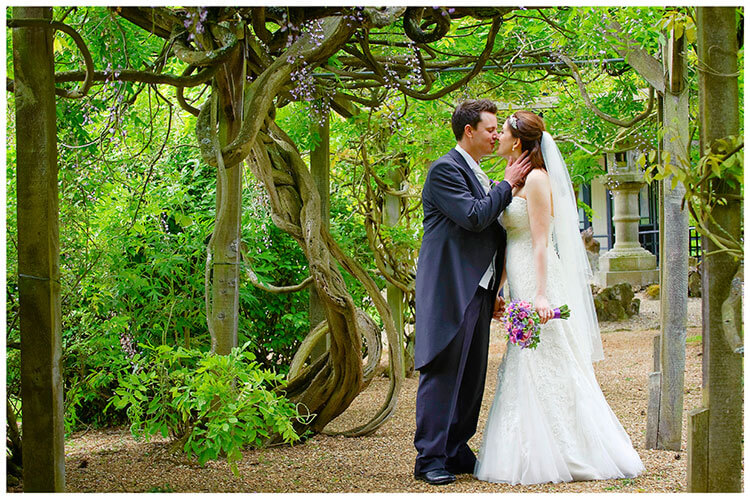 Fanhams Hall wedding bride groom romantic moment under wisteria
