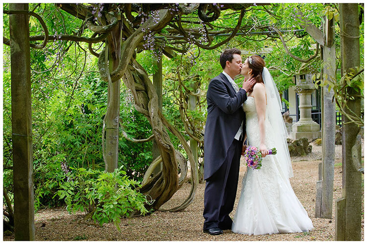 Fanhams Hall wedding bride groom romantic kiss under wisteria