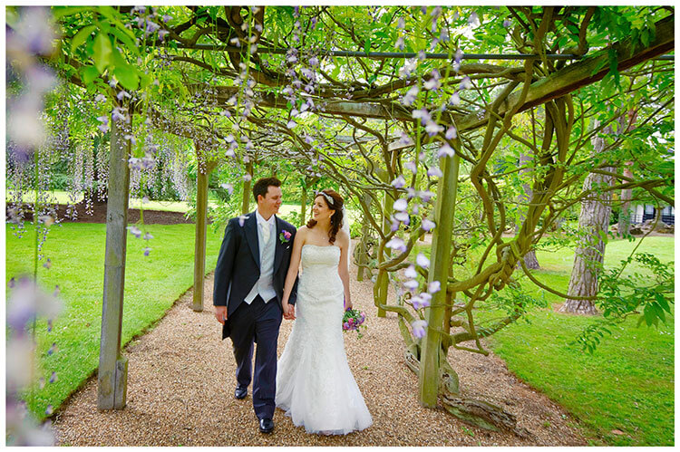 Fanhams Hall wedding bride groom walking under wisteria walkway