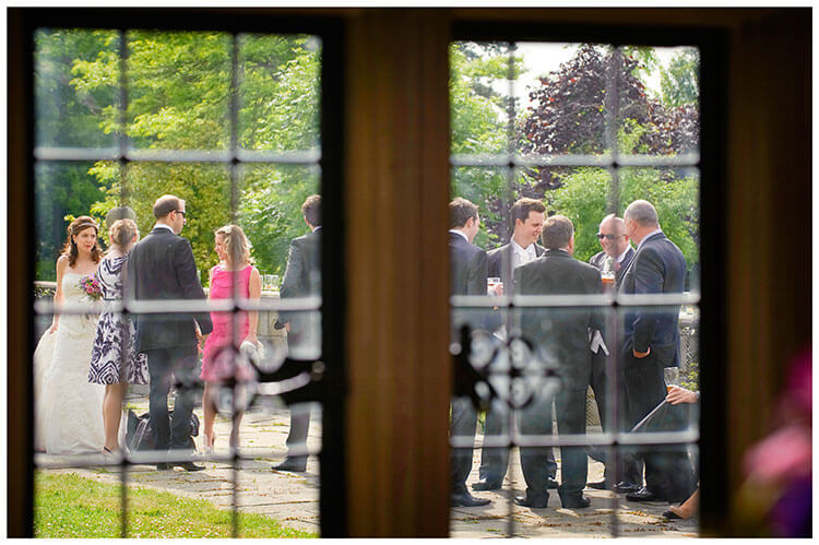 Fanhams Hall wedding guests bride groom viewed through window