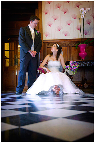 Fanhams Hall wedding groom talks to sitting bride chechered floor