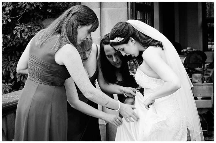 Fanhams Hall wedding bride checks torn dress with friends