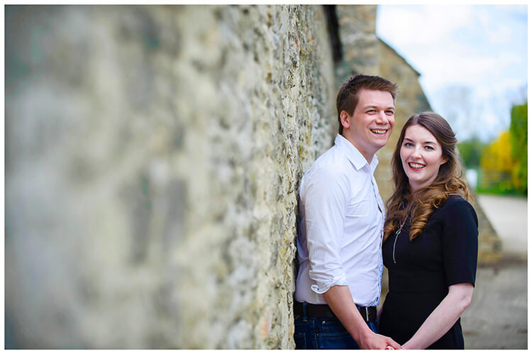 Friars Court Oxfordshire Pre-Wedding Photoshoot  romantic couple embrace leaning against wall
