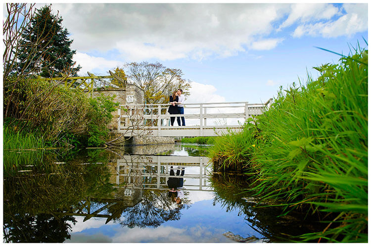 Friars Court Oxfordshire Pre-Wedding Photoshoot  romantic couple stood on bridge reflected in stream