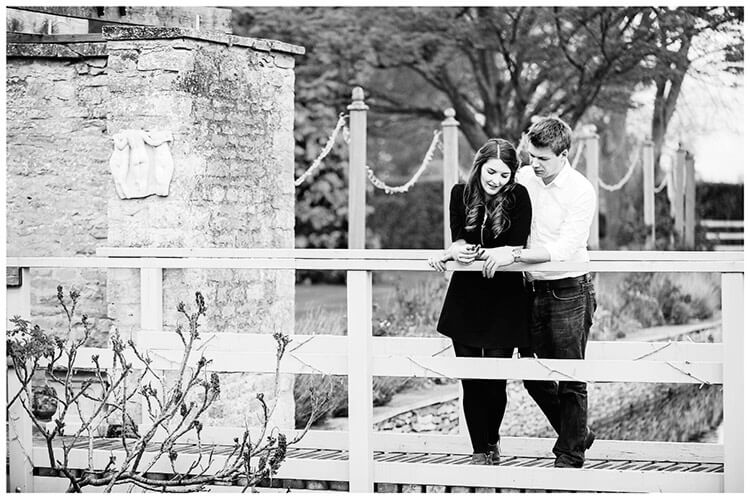 Friars Court Oxfordshire Pre-Wedding Photoshoot  bride to be shows partner engagement ring standing on bridge