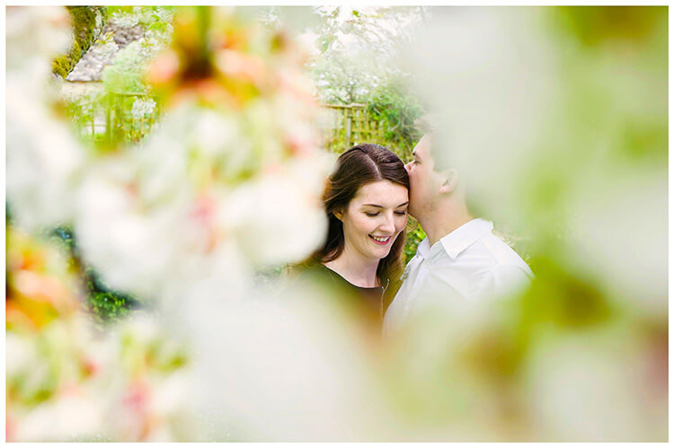 Friars Court Oxfordshire Pre wedding photoshoot  couple embrace amongst blossom