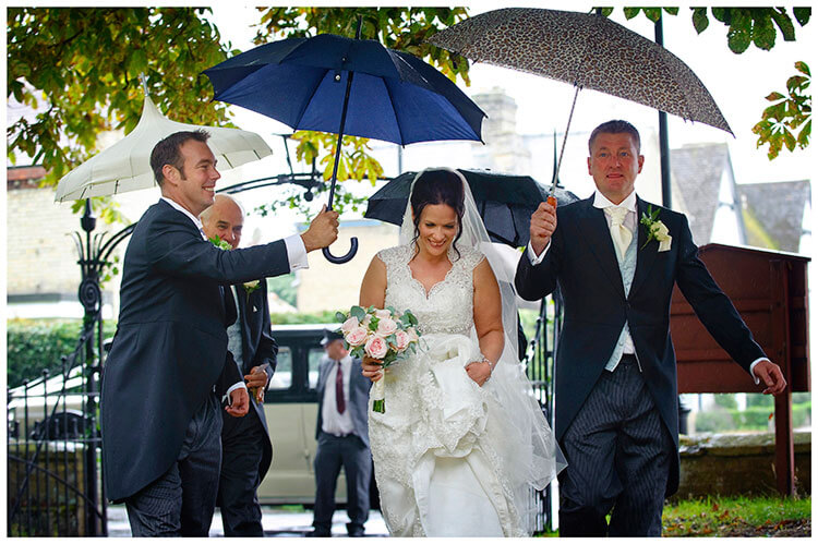 Longstowe Hall Wedding bride under cover from rain