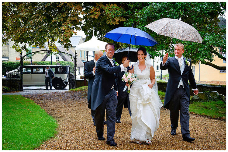 Longstowe Hall Wedding smiling bride arrives at church under umbrellas