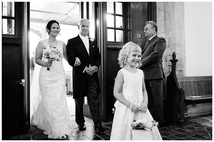 Longstowe Hall Wedding bride and her father enter church with smiling flowergirl
