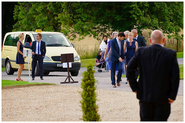 Madingley Hall Wedding taxis dropping off guests watched by porter