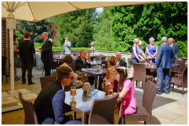 Madingley Hall Wedding guests enjoying a drink before the ceremony