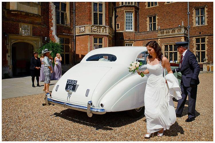 Madingley Hall Wedding bride walking around car holding bouquet