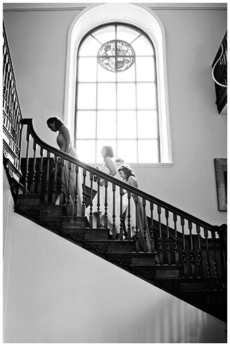 Madingley Hall Wedding bridal party going up stairs large window