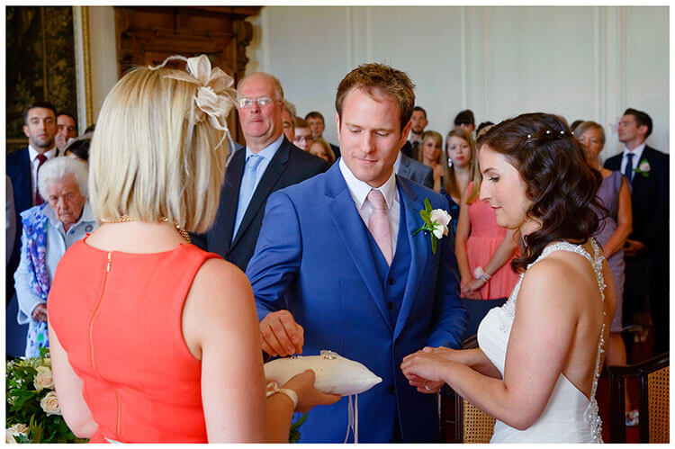 Madingley Hall Wedding groom takes wedding band to place on brides finger