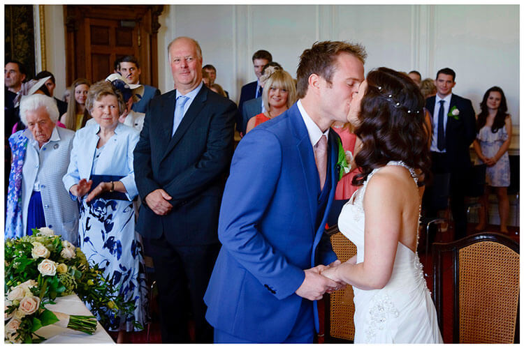 Madingley Hall Wedding bride groom kiss at end of ceremony
