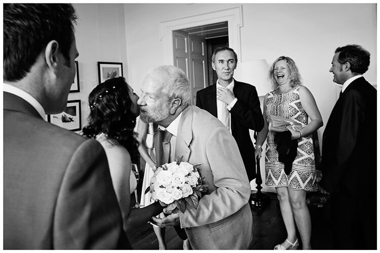 Madingley Hall Wedding guest gives bride a kiss