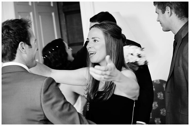 Madingley Hall Wedding female guest about to hug groom