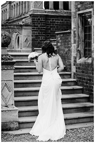 Madingley Hall Wedding bride walking up steps holding bouqett