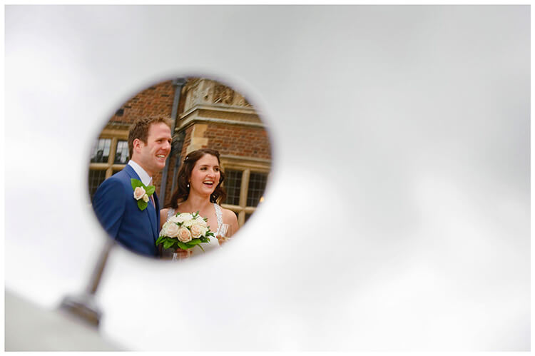 Madingley Hall Wedding smiling bride groom reflected in car wing mirror
