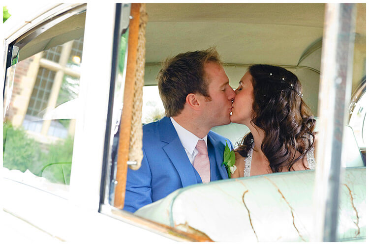 Madingley Hall Wedding bride groom kiss in car