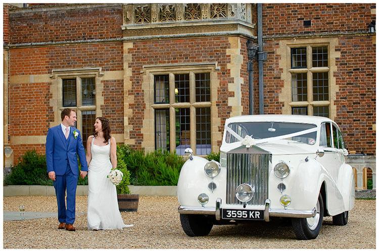 Madingley Hall Wedding bride groom walking past white wedding car