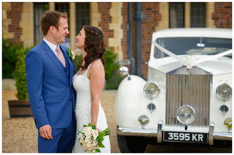 Madingley Hall Wedding bride groom infront of car