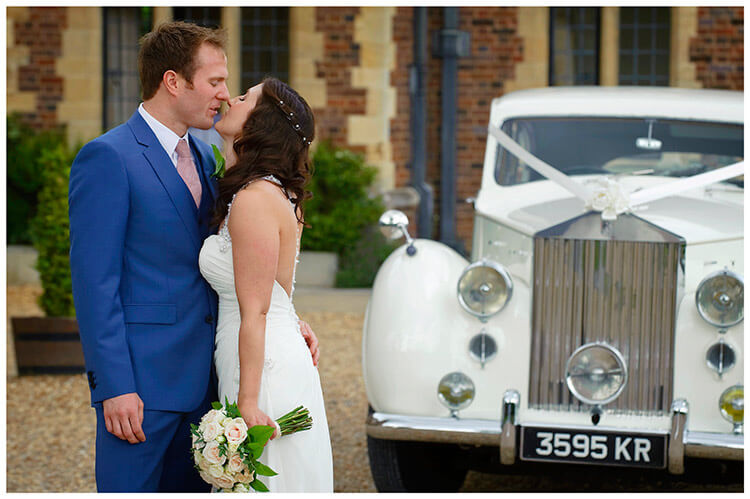 Madingley Hall Wedding bride groom kiss in front of car