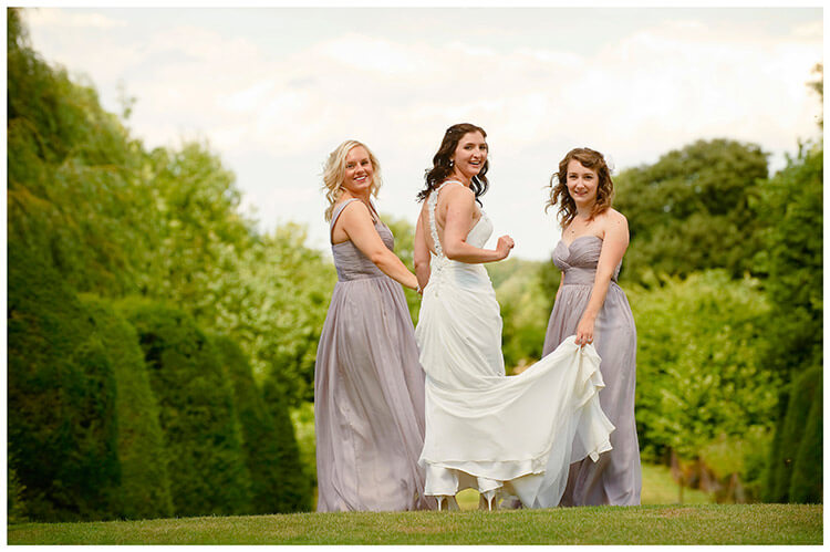 Madingley Hall Wedding bride looking over shoulder accompanied by two bridesmaids