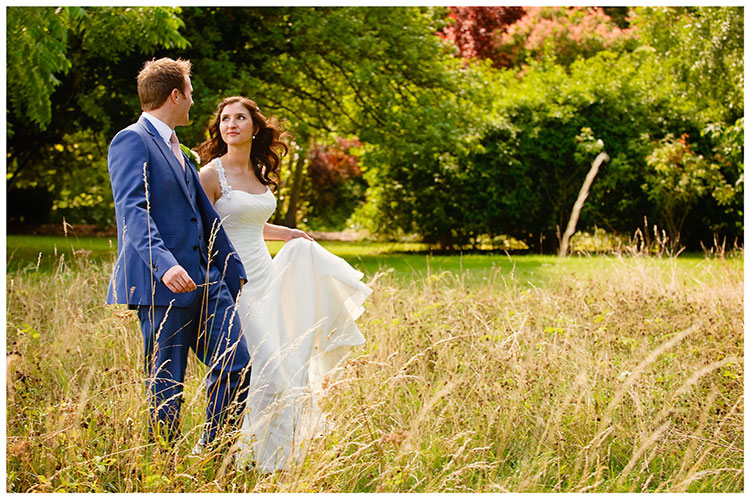 Madingley Hall Wedding bride groom in long grass