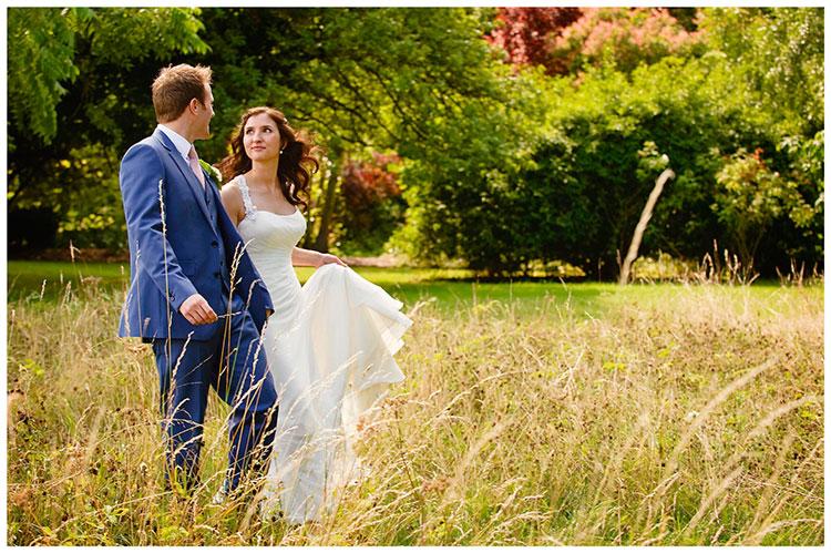 Madingley Hall Wedding bride groom in long grass