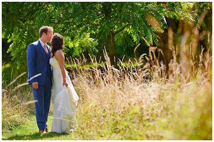 Madingley Hall Wedding bride groom kiss in gardens