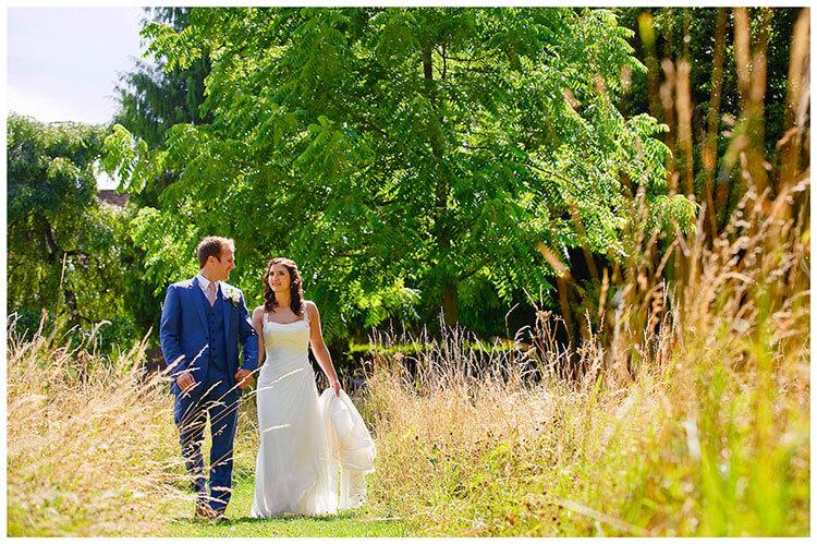 Madingley Hall Wedding bride groom walking along footpath long grass