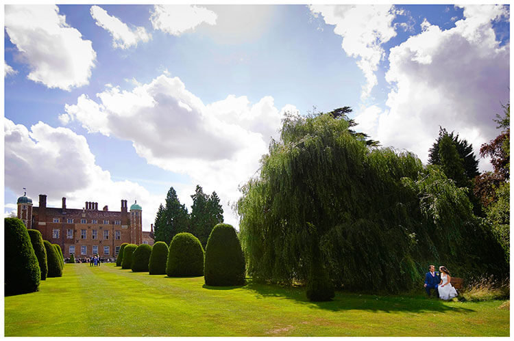 Madingley Hall Wedding sitting on bench in gardens under a bright blue sky