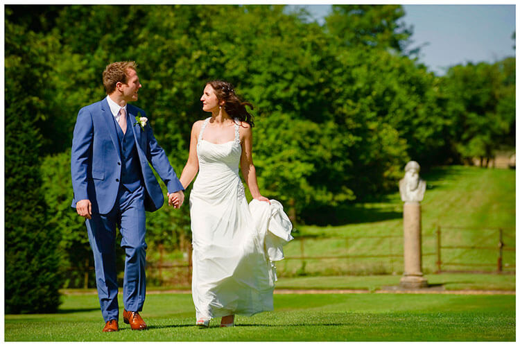 Madingley Hall Wedding bride groom look at each other walking in gardens holding hands