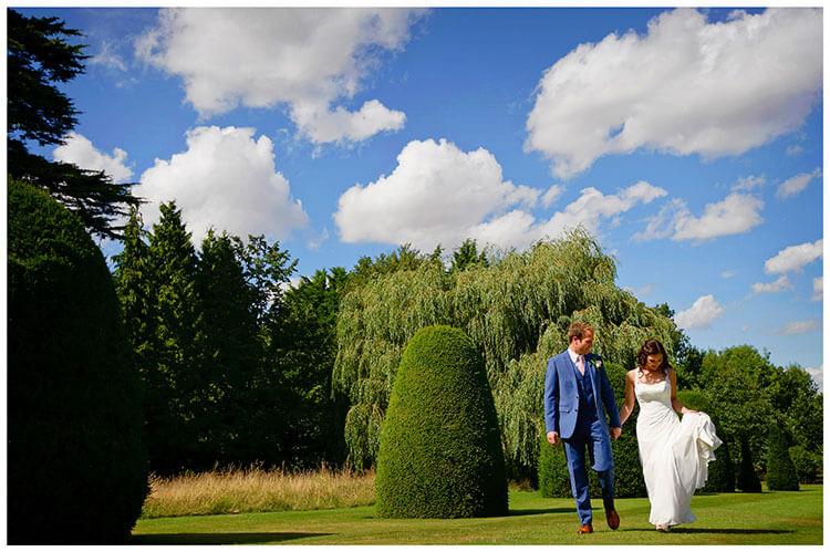 Madingley Hall Wedding bride looking at dress as she walks with groom