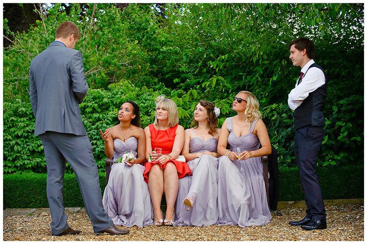 Madingley Hall Wedding bridesmaids sitting on garden bench
