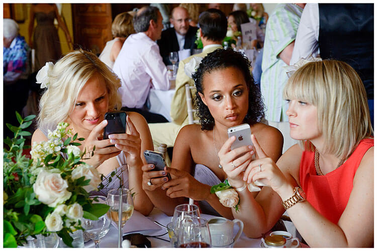 Madingley Hall Wedding checking their phones