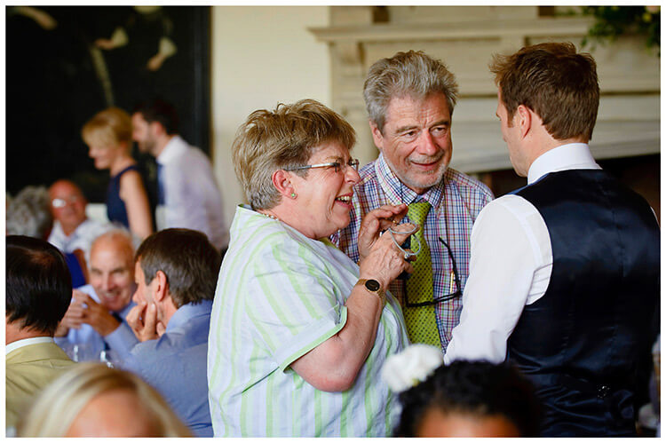 Madingley Hall Wedding guests in conversation with groom