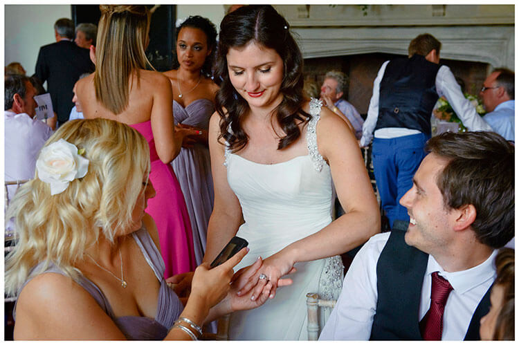 Madingley Hall Wedding bride showing wedding band as bride maid takes a photo on her phone