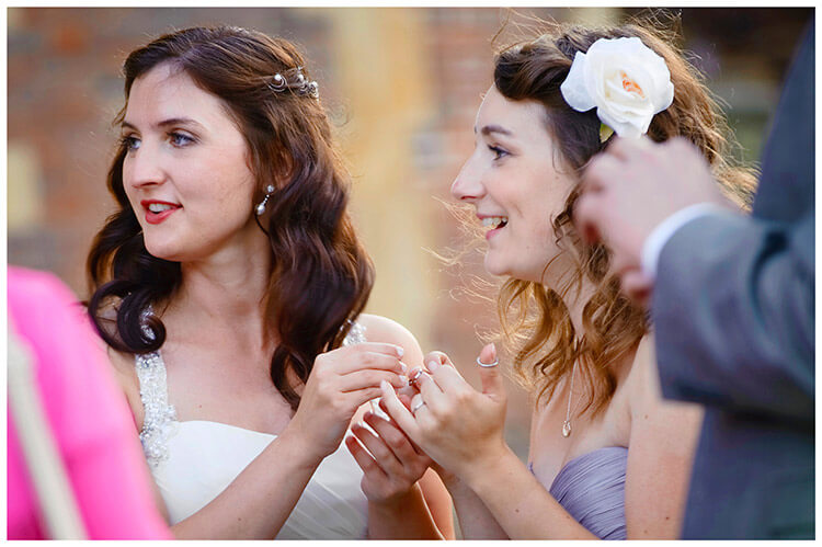 Madingley Hall Wedding bride shows wedding bands to brides maid